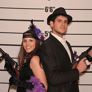Detroit Murder Mystery party guests pose for mugshots